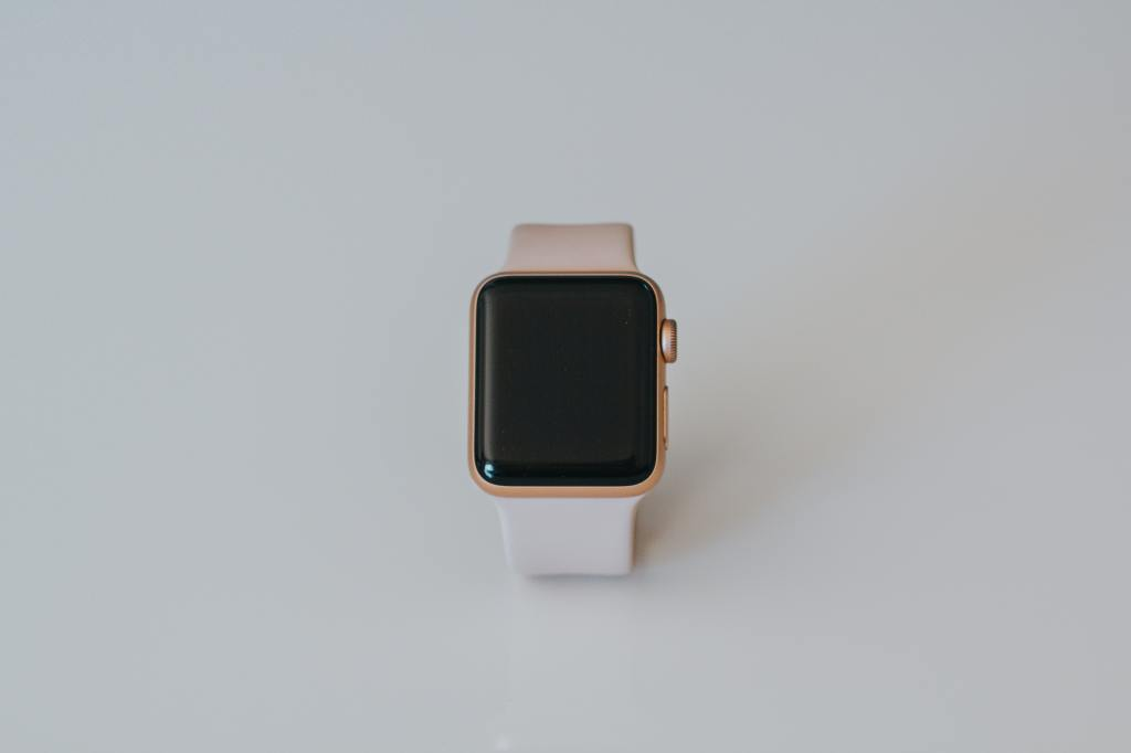 Image of peach colored Apple Watch series 5 on plain white background.  Photo by Marcin Nowak on Unsplash